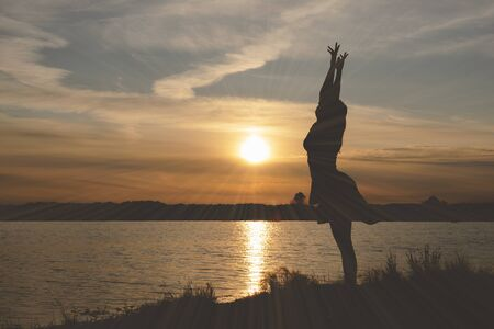 Silhouette of young dancing woman in sunset rays on a lake shore.