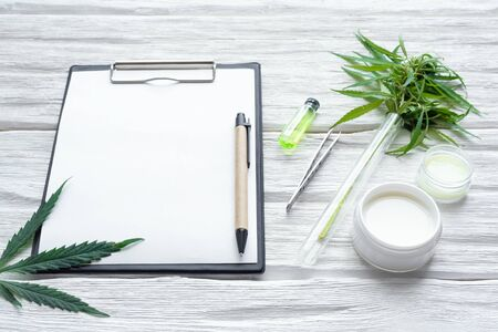 Cannabis cosmetic cream in a jar and a blank paper page with a copy space and a green hemp leaf on a white wooden table background.