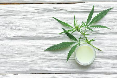 Cannabis cosmetic cream in a jar and a green plant leaf on a white wooden table background. Natural cosmetic.