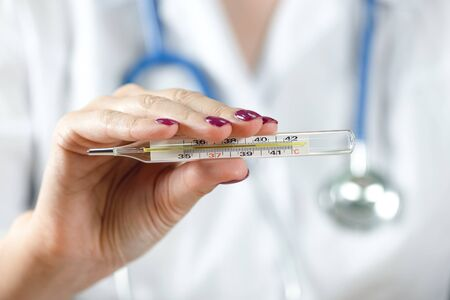 Doctor woman showing thermometer with a high body temperature. Stock Photo