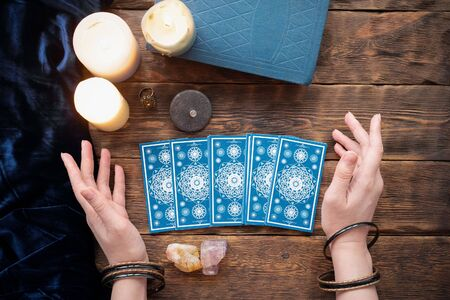Fortune teller with tarot cards in the hand on brown table background. Reklamní fotografie