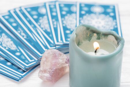 Blue tarot cards deck and burning candle close up.