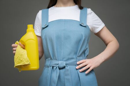 A cleaner woman is standing with detergent bottle and yellow rag in her hands close up.