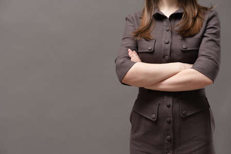 Strict woman boss is standing with crossed hands close up on gray background with copy space. Foto de archivo