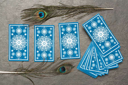 Blue tarot cards on the stone table surface background.