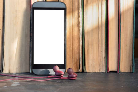 Mobile phone with blank screen with copy space and old books. Electronic book concept.