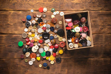 Heap of retro style sewing buttons on the cardboard box on the wooden table flat lay background.