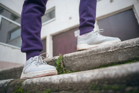 Female feet in the sneakers on the stairs close up.