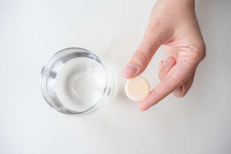 An ascorbic acid tablet in female hand and glass of water.