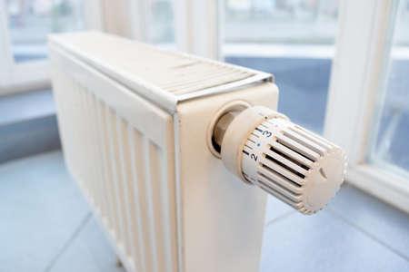 White modern heating radiator on the window background. Banco de Imagens
