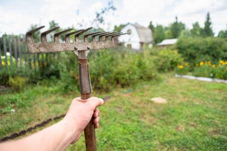 Rake in the gardener hand on the garden background.