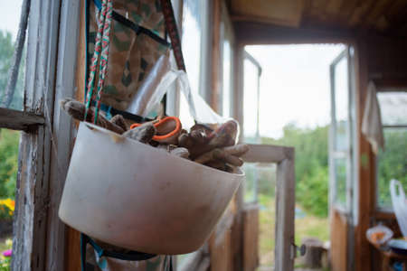 Old garden gloves in the collecting container close up on the garden house interior background.