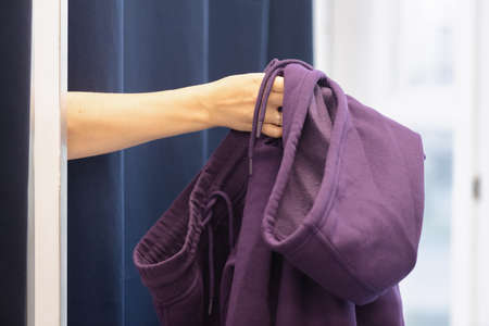 Woman is showing a wrong size clothes from fitting room close up. Banco de Imagens