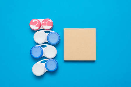 Contact lenses containers and blank page notes on the blue flat lay background. Banco de Imagens