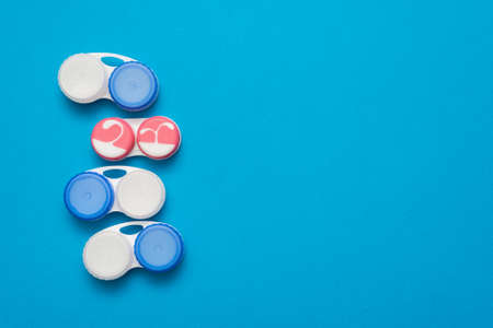 Contact lenses containers on the blue flat lay background. Banco de Imagens