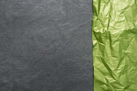 Green crumpled paper page on the gray stone background top view with copy space.