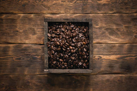 Roasted coffee beans in the wooden box container on the brown table background. Banco de Imagens