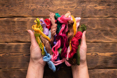 Colorful embroidery threads in female hands on the brown table background.