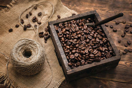Roasted coffee beans in the wooden box container on the brown table background Banco de Imagens