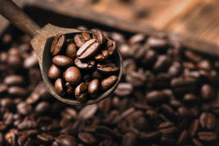 Coffee beans in the wooden scoop close up.