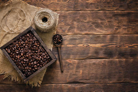 Roasted coffee beans in the wooden box container on the brown table background with copy space. Banco de Imagens