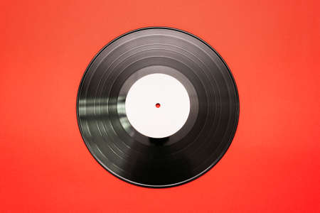 Old vinyl record on the red flat lay background.