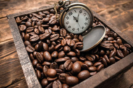 Pocket watch and coffee beans in the wooden box container close up. Coffee break concept. Banco de Imagens