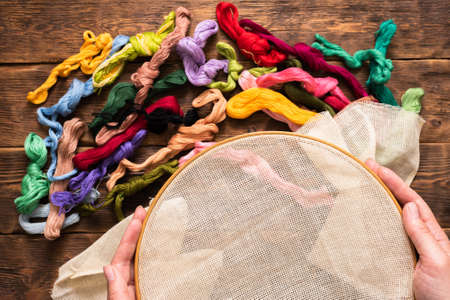 Hoop and colorful threads on the brown wooden table background. Banco de Imagens