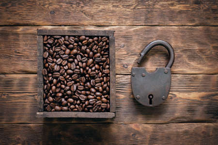 Secrets of coffee concept. Old padlock and coffee beans in the wooden box container on old wooden table background.