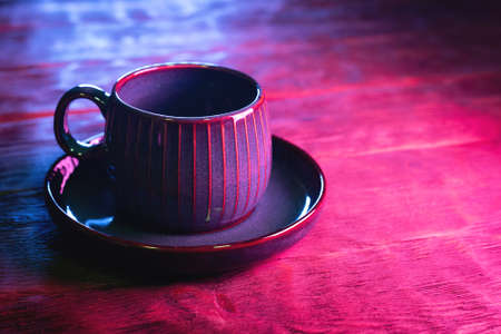 Coffee cup on the wooden table background in neon lights close up.