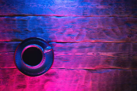 Coffee cup on the wooden table background in neon lights. Banco de Imagens