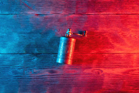 Small pepper mill on the table in the neon light background.