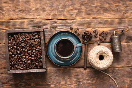 Coffee cup and coffee beans in the wooden container box on the table.