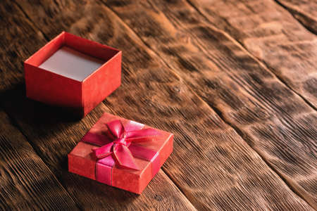 A small red gift box with open cover on the wooden table background.