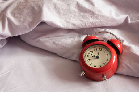 Red alarm clock on the bed blanket background close up. Stockfoto