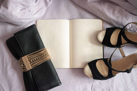 High heels shoes, clutch bag and blank page diary on the bed blanket background top view.