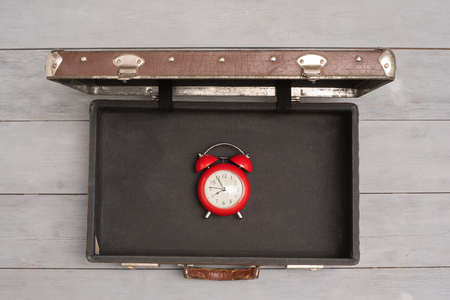 Suitcase with a red alarm clock within abstract background. Travel time concept.
