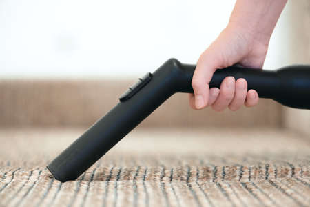 Woman is cleaning the furniture from the dust by the vacuum cleaner close up.