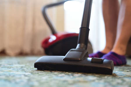 Woman is cleaning the floor by the vacuum cleaner close up. Stockfoto