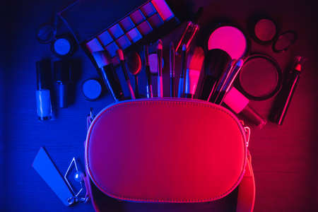 Various makeup accessories and cosmetics on the flat lay table background.