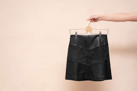 Woman is holding in hand a black skirt on the hanger on the light background.