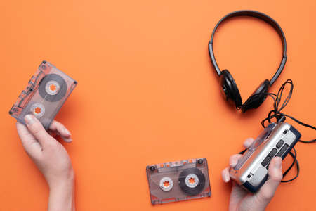 Old retro stereo cassette player and headphones on the orange flat lay background.