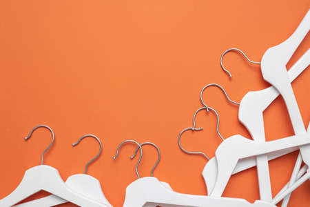 White clothes hanger on the orange flat lay background with copy space.