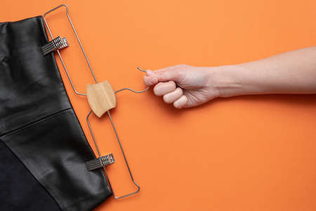 Woman is holding in hand a hanger with a black leather skirt on the orange flat lay background.