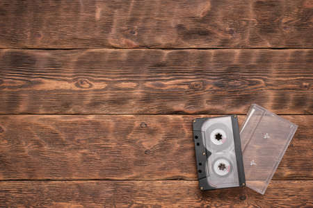 Old retro cassette on the brown wooden table background. Stockfoto