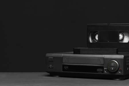 Video recorder and video tapes on the table on the black background.
