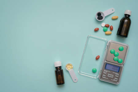 Tablets, medical bottles and small electronic weights on the blue background. Pharmacology. Stockfoto