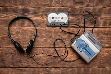 Portable retro stereo cassette player, old headphones and cassettes ont he brown wooden table background.