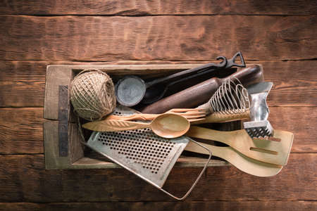 Old kitchen utensils on the brown wooden table background.