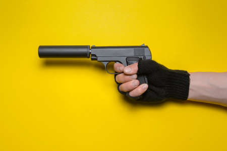 A toy pistol with a silencer in the male hand isolated on yellow background.